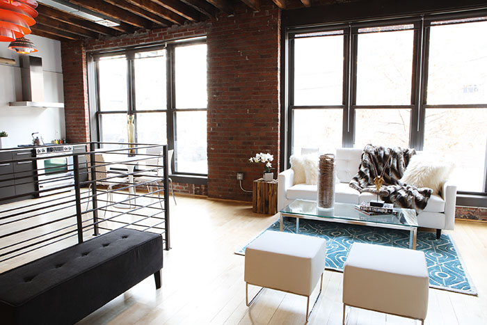 Wood accents like a wood side table and tall vessel filled with rope create interesting conversation pieces in this industrial style loft space. (Handout/TNS)