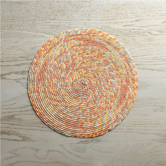 Kaleidoscope Placemat  A kaleidoscope of sunset tones spiral in this textural round placemat made of dyed, braided and woven paper. Lightweight and flexible, the casual, colorful placemat is ideal for everyday use.