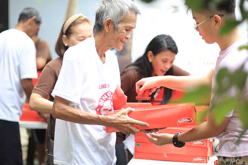 An elderly man receives his Triple Chocolate Roll, a heartwarming gift this holiday season.
