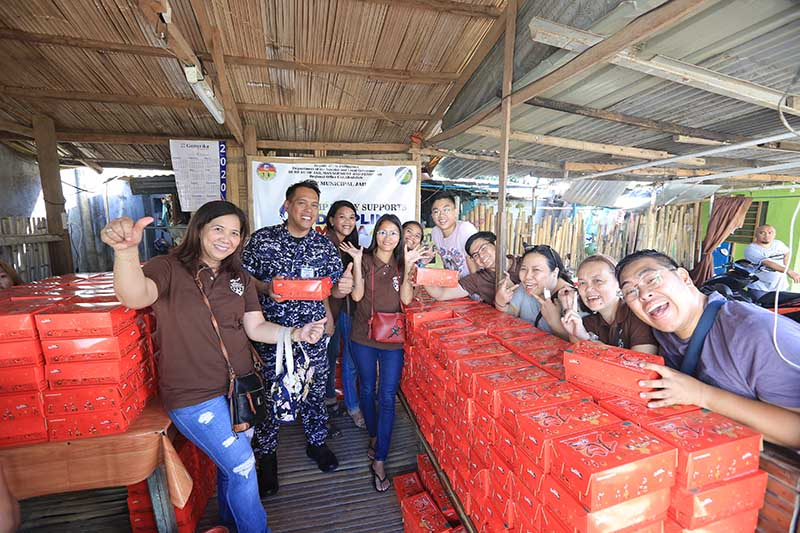 Lay volunteers of The Mount Carmel Sisters pose with Tanay Municipal Jail officer while preparing the Triple Chocolate Rolls for distribution.
