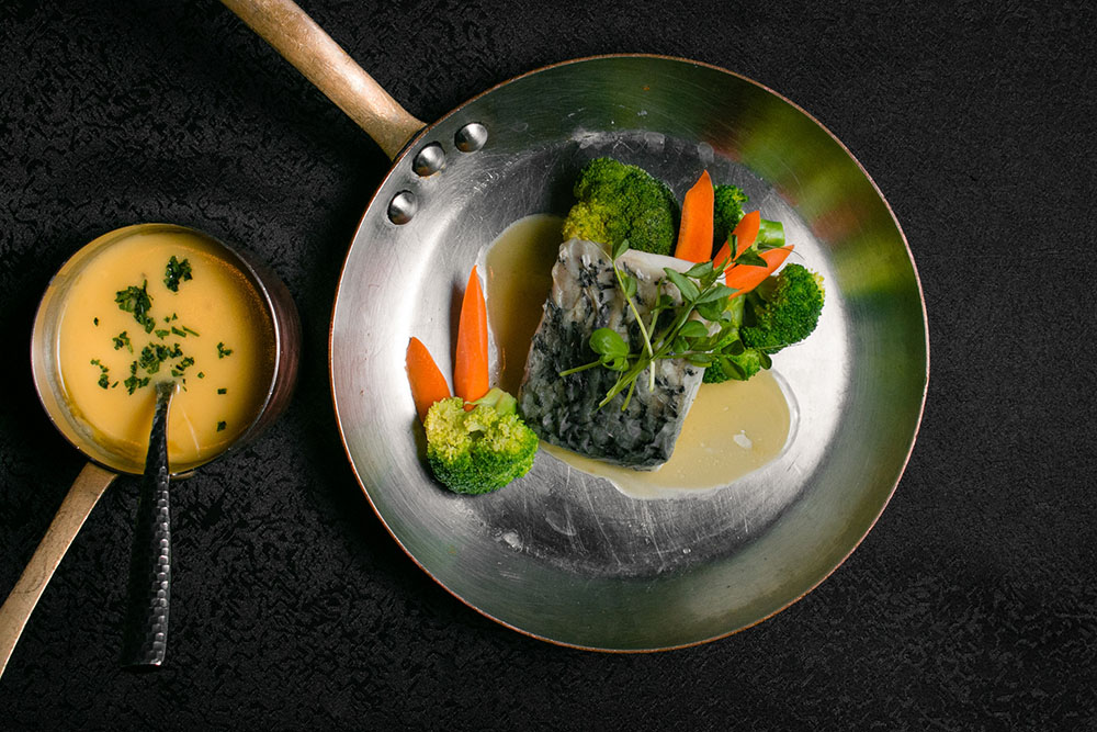Poached fish with white butter sauce and broccoli