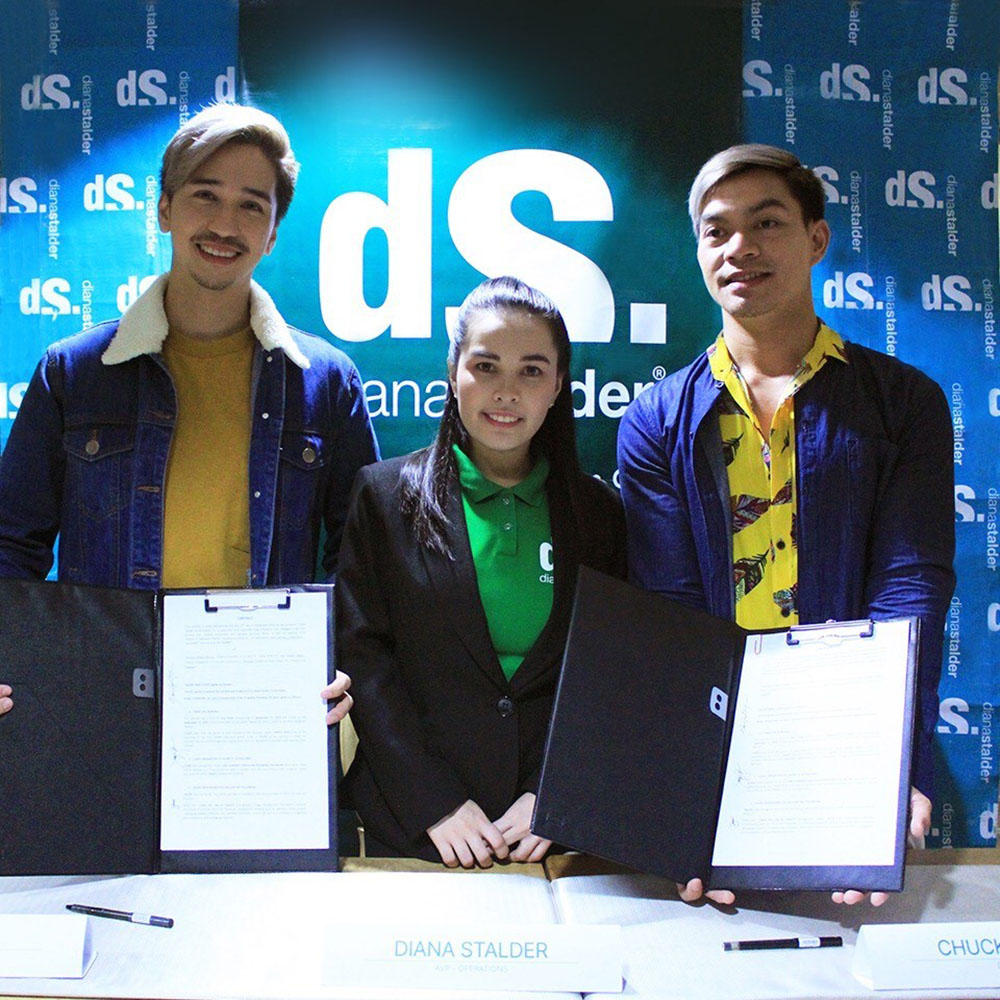 Social Media Influencers Joe Abad (left) and Chuck Aquino (right) ink contract with skincare brand Diana Stalder, shown here flanking Diana Stalder, Assistant Vice-President for Operations of Diana Stalder Face, Body, Skincare, and Café.