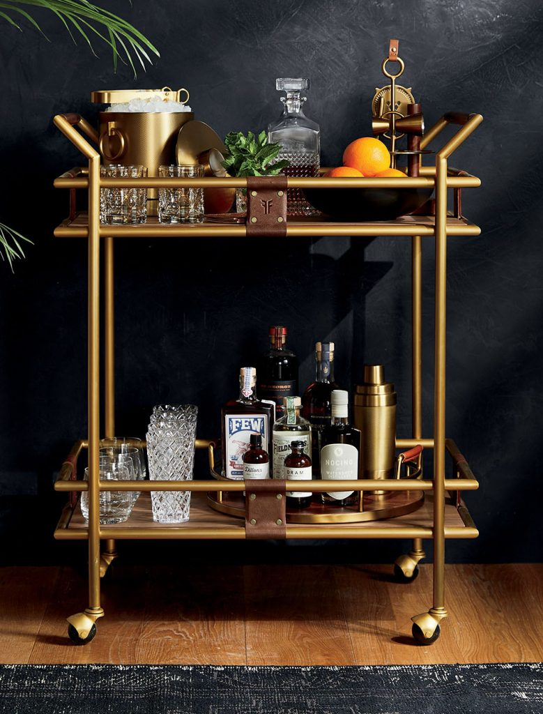 This Frye 2-Tier Bar Cart showcases bar accessories, sparkling glassware and prized spirits as part of Crate&Barrel's exclusive collaboration with leather goods legend Frye. The wheeled cart boasts leather and gold accents. Handles wrapped in genuine cognac leather provide a sturdy grip on a brass-plated cart finished in antiqued gold, while two gorgeously grained acacia wood shelves provide plenty of room for cocktail essentials. The bar cart also functions as an upscale coffee cart in the kitchen, or in your office as a chic printing station.
