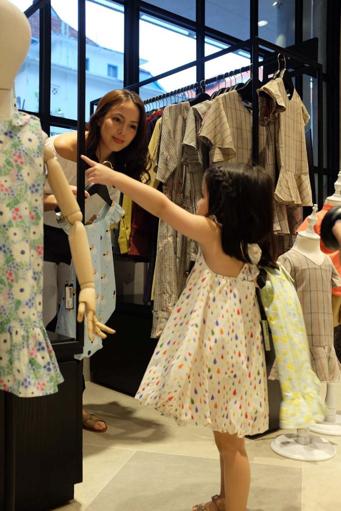 Andi and Olivia choose from a collection of adorable children's clothing at their new favorite shop, Chubby Chubby, at Design Orchard.
