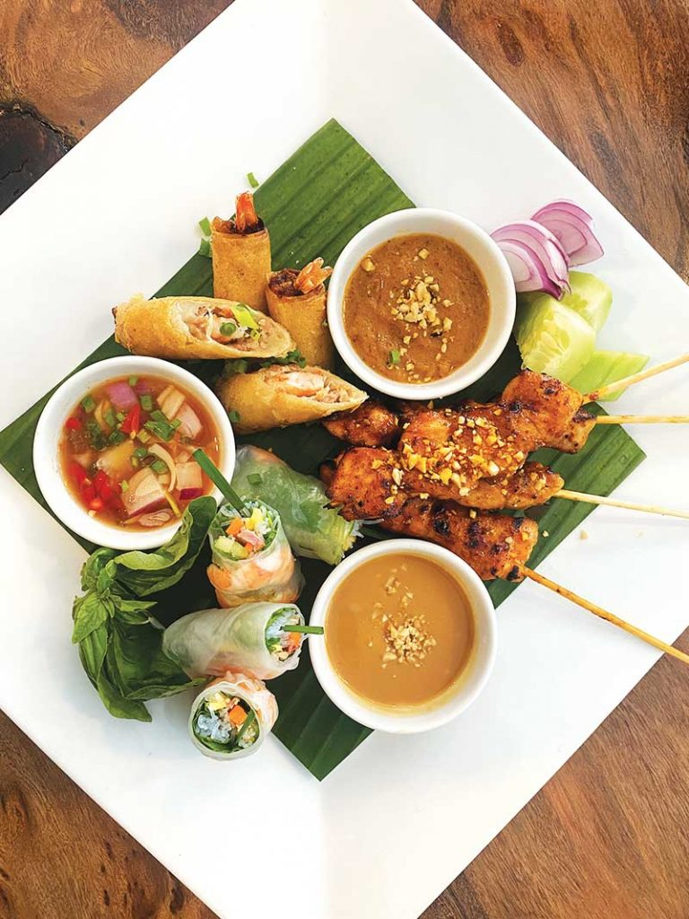 A platter of Pandan Cafe's appetizers consisting of Vietnamese fresh and fried spring rolls and chicken satay.